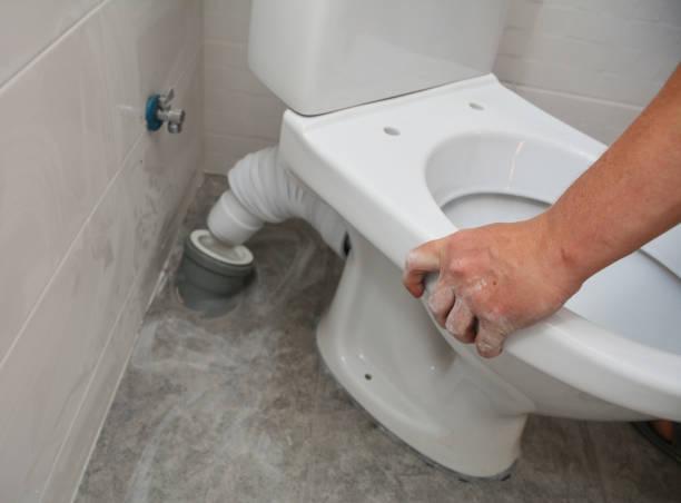 um vaso sanitário branco, instalação de assentos e encanamento que conecta o conector da panela do vaso sanitário ao tubo de resíduo e tubo de abastecimento de água ao tanque do vaso sanitário no canto do banheiro. - banheiro instalação doméstica - fotografias e filmes do acervo