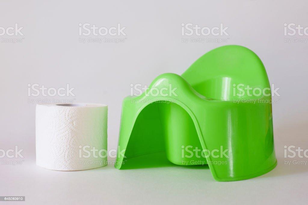 Papel higiénico blanco y pila de pañales al lado verde al baño sobre fondo blanco - foto de stock