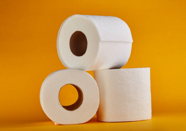 white toilet paper rolls on vivid yellow / orange background - carta igienica foto e immagini stock