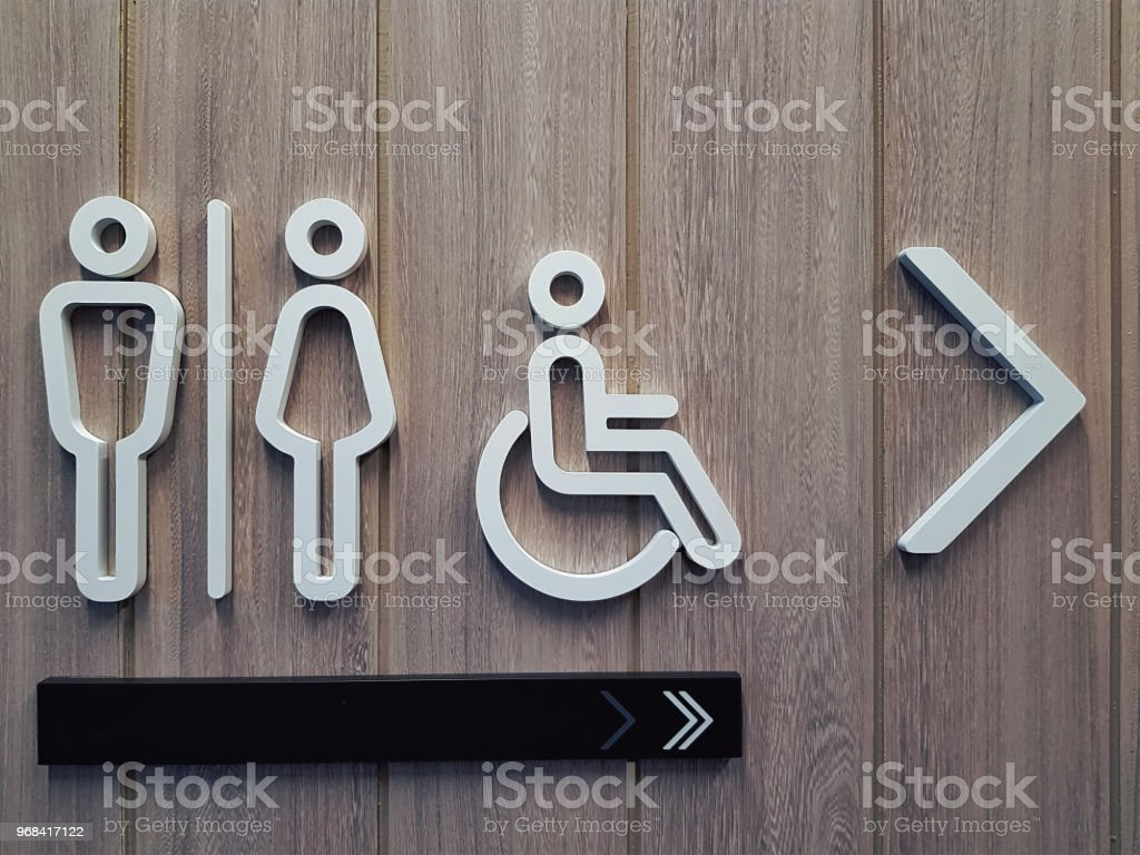 White Toilet Symbols on Wooden Plank Wall stock photo