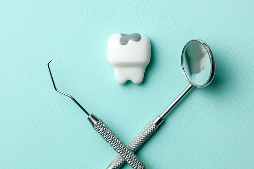 istock White tooth with caries on green mint background  and dentist tools mirror, hook. 1133134441