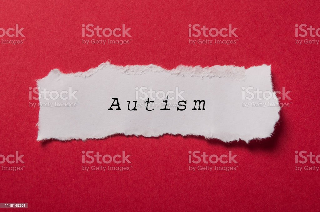 white torn paper on red paper background - Autism stock photo