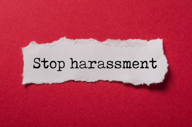 white torn paper on red paper background with text - Stop harassment closeup of white torn paper on red paper background with text - Stop harassment harassment stock pictures, royalty-free photos & images