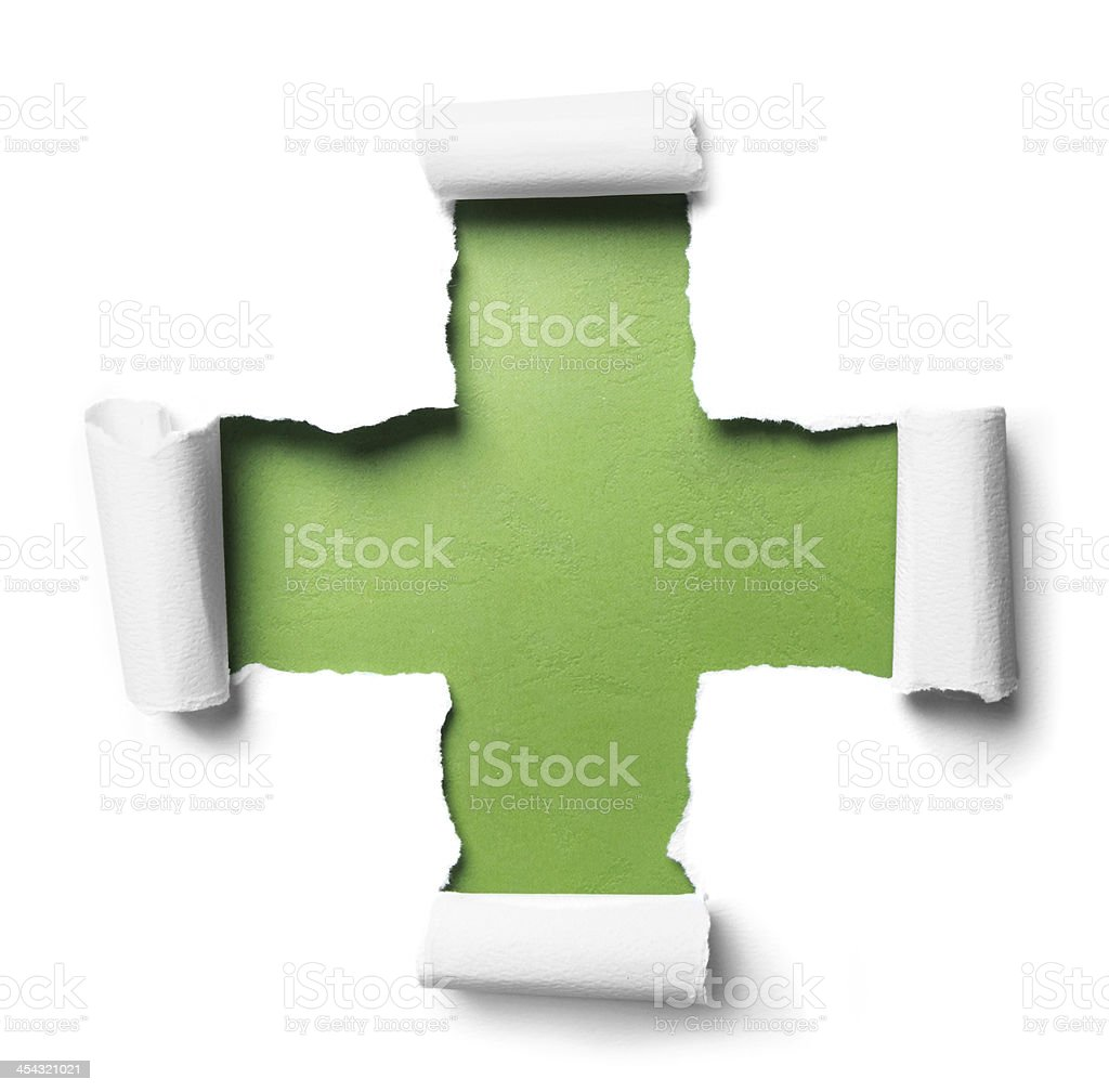 White torn paper with plus shape over green stock photo