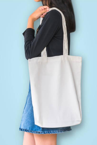 weiße tasche modell vorlage baumwolle stoff leinwandstruktur auf mädchen schulter (isoliert mit beschneidungspfad) auf blauem hintergrund - kinderhandtaschen stock-fotos und bilder