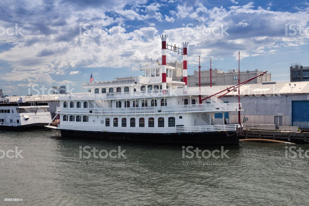 White Tourboat Moored at Red Hook Pier and Cloudy Blue Sky, Brooklyn, New York. stock photo
