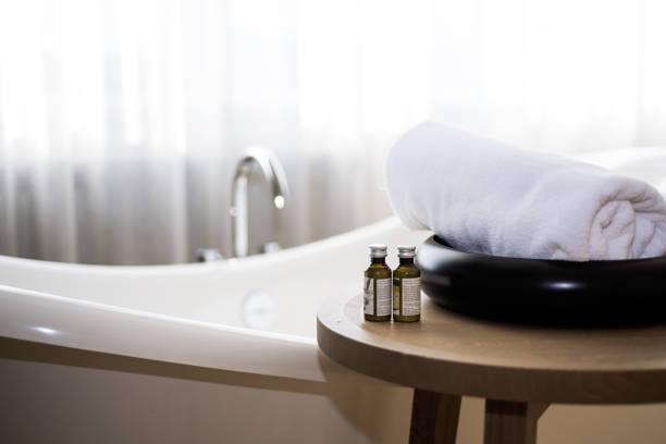 weißes handtuch und massage badeöl auf tisch im badezimmer. - sonnendusche stock-fotos und bilder