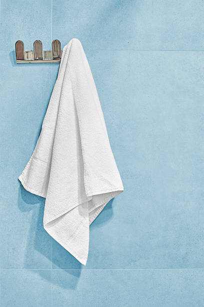 White towel hanging on a wall in bathroom. stock photo