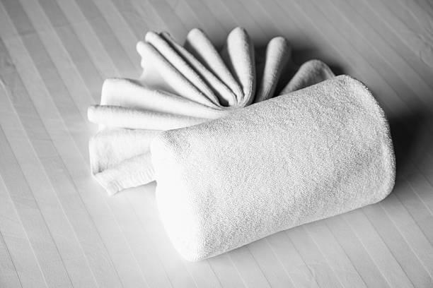 weiße handtücher auf dem bett im schlafzimmer entspannung - badewannenkissen stock-fotos und bilder
