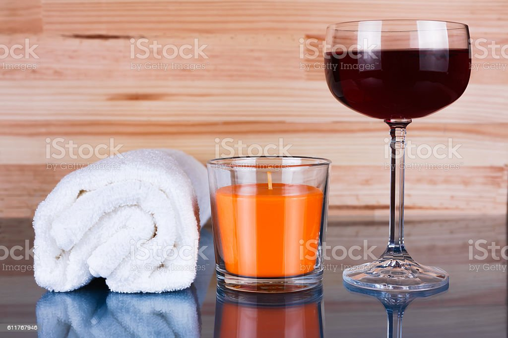 White towel, orange candle and a glass of wine. stock photo