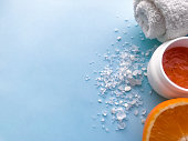 istock White towel rolled in a roll, a jar of orange scrub, pile of sea salt, half of orange on a blue background, copyspace. The concept of the SPA, anti-cellulite 1207967897