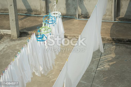 White towels and sheets dry in the sun. White clothes hung out to dry on a washing line