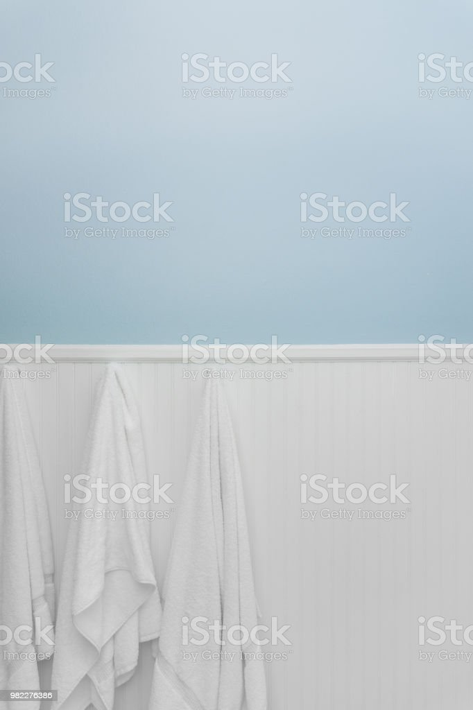 White towels hanging on white bead board or wainscot stock photo