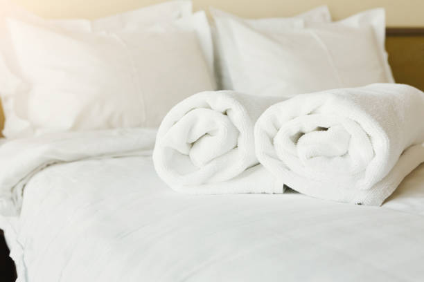 White towels on bed in hotel bedroom closeup stock photo