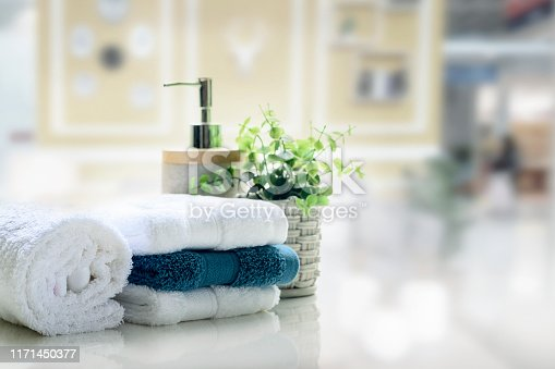 White towels on white top table with copy space on blurred living room background. For product display montage.