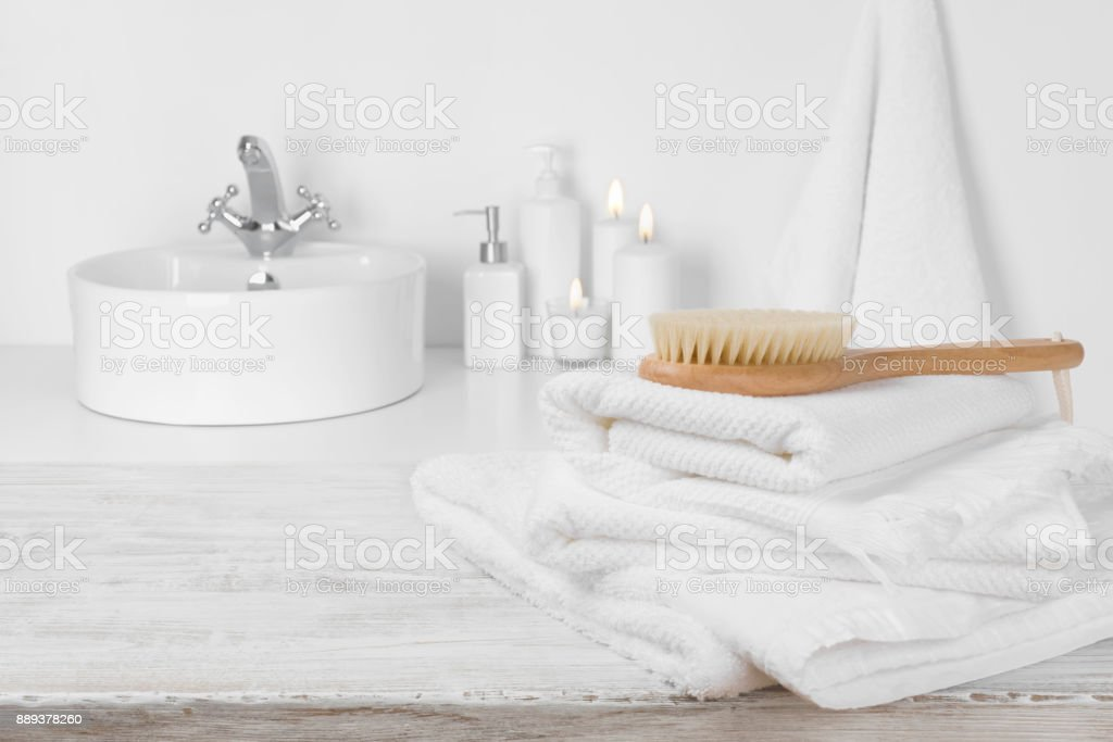 White Towels On Wooden Table Over Blurred Simple Bathroom Background Royalty Free Stock Photo