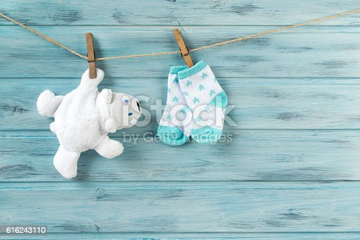 istock White toy bear and baby socks with stars on clothesline 616243110