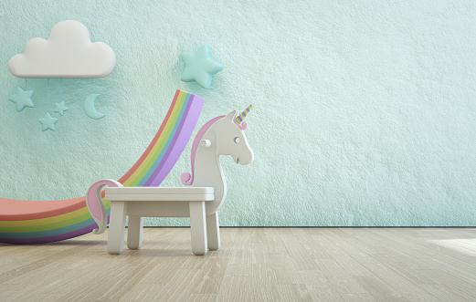 istock White toy unicorn on wooden floor of kids room with empty rough blue concrete texture wall background. 1018082358