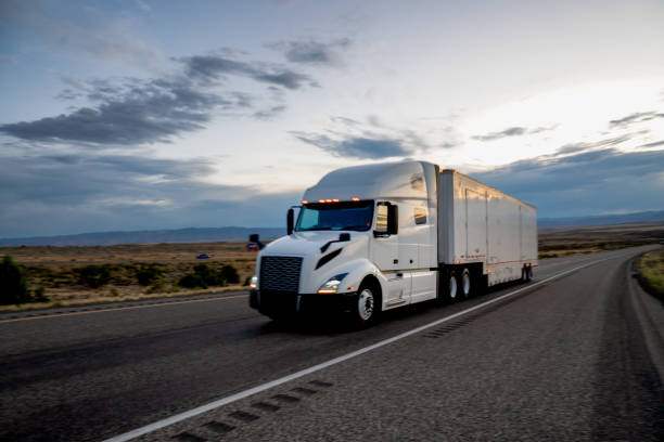 White Tractor, Semi-Trailer Freight Truck Rolling Down the Highway under a Dramatic Sky stock photo