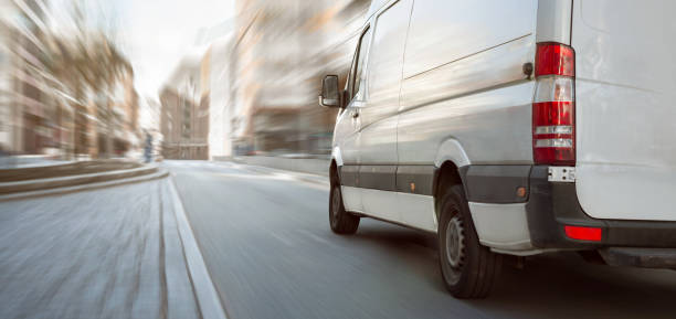 White transporter driving inside the city A fast moving white van on a bright street with high buildings. Motion blurred background. commercial land vehicle stock pictures, royalty-free photos & images