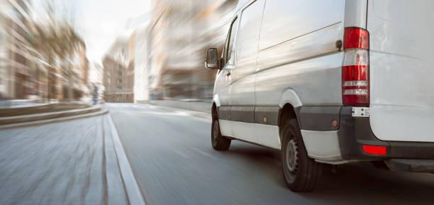 white transporter driving inside the city - entregar imagens e fotografias de stock