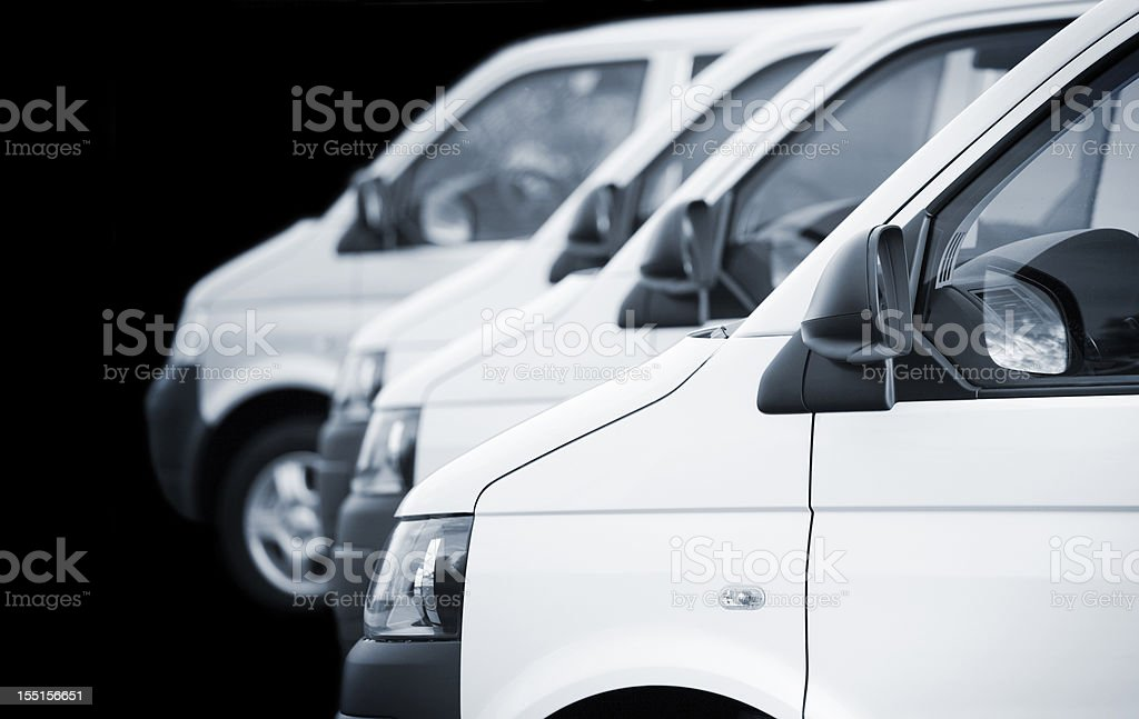 White transporters / vans in a row on black background stock photo
