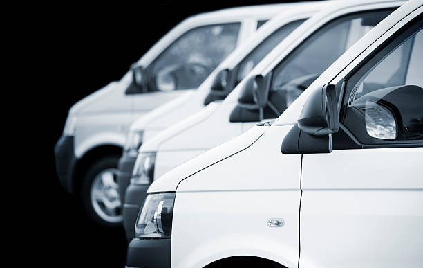 white transporters / vans in a row on black background - wheel black background bildbanksfoton och bilder