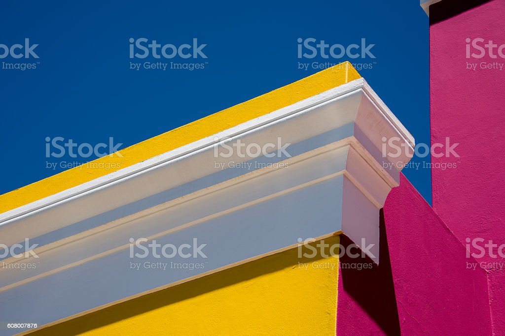 white trim,  yellow and pink house, and deep blue sky. stock photo