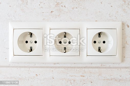 White triple electrical outlet on the textured wall.
