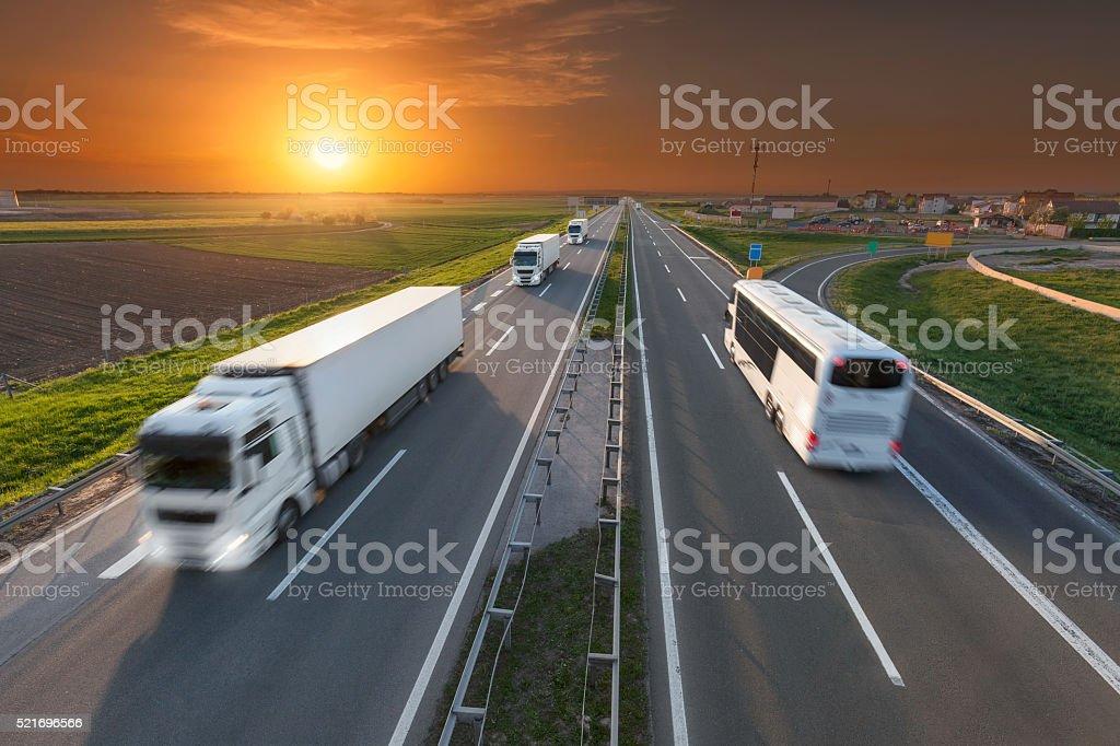 Blanco, camiones y autobuses en la carretera al anochecer - foto de stock