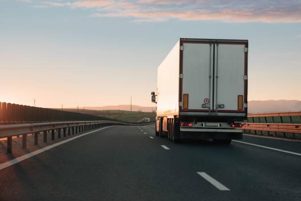 Weißen LKW-fahren auf der leeren Autobahn während des Sonnenuntergangs – Foto