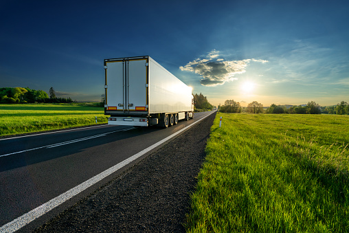 White truck driving on the asphalt road in a spring rural landscape at sunset