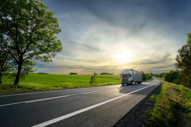 weißen lkw-fahren auf der asphaltierten straße neben dem grünen feld in ländlichen landschaft bei sonnenuntergang - schweres nutzfahrzeug stock-fotos und bilder