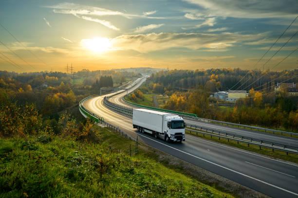 weißen lkw-fahren auf der autobahn schlängelt sich durch bewaldete landschaft in herbstlichen farben bei sonnenuntergang - schweres nutzfahrzeug stock-fotos und bilder