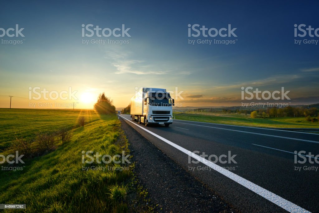 White truck driving on the road in landscape at sunset stock photo