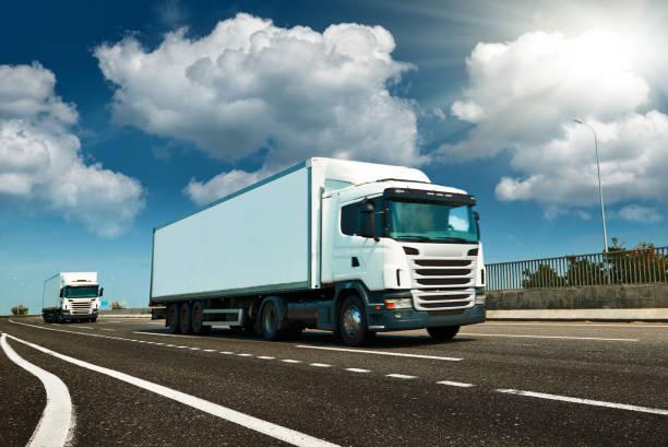 Camión blanco está en carretera - negocios, comercial, concepto de transporte de carga, espacio libre y en blanco en la vista lateral - foto de stock