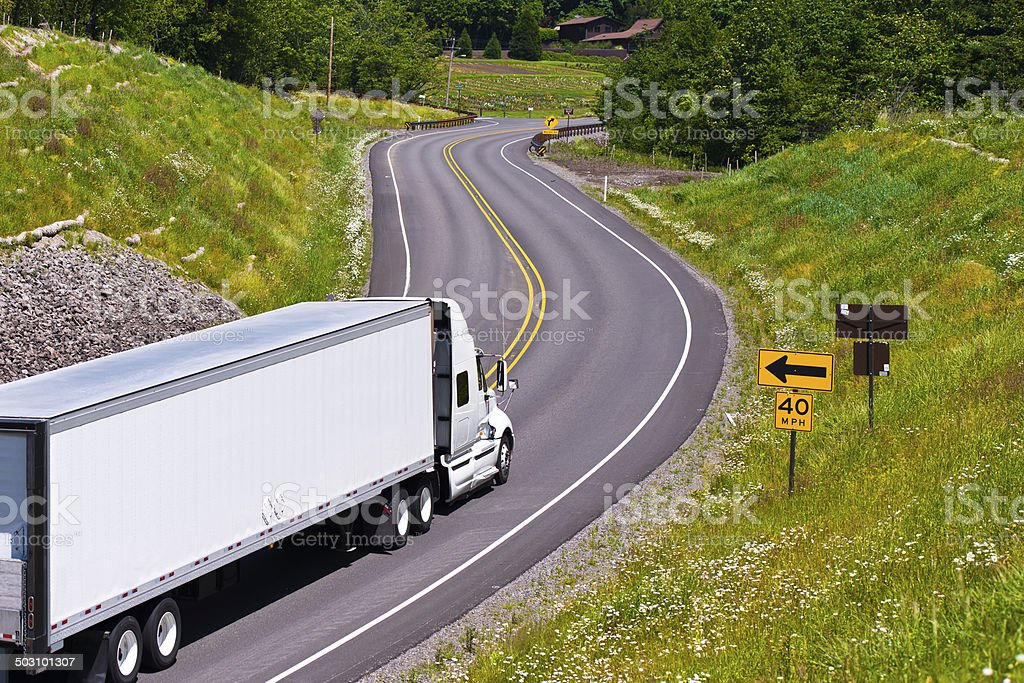 White truck trailer on winding road between green hills stock photo