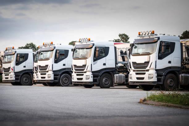 weiße lastwagen hintereinander geparkt - motionless in white stock-fotos und bilder