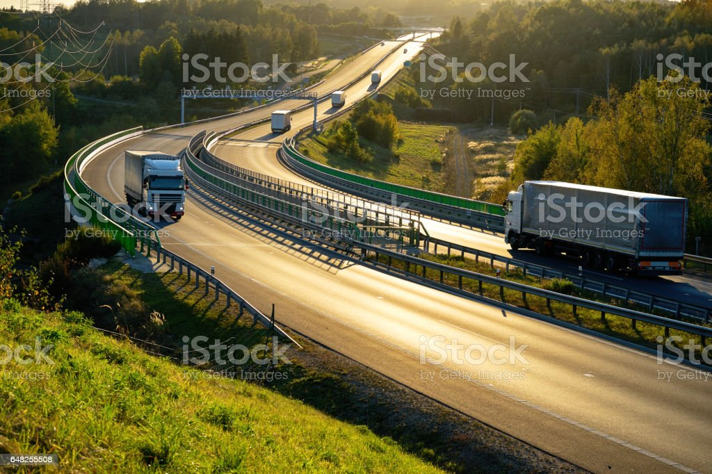 White trucks passing through tollgates on the highway in backlit stock photo