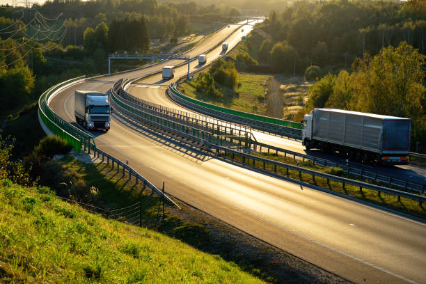 white trucks passing through tollgates on the highway in backlit - land vehicle stock photos and pictures