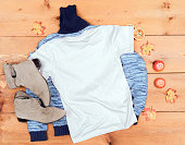 istock White T-shirt and a Sweater on a Wooden Background 1039641272
