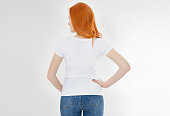 istock white t-shirt on a smiling girl : back view. Red hair woman with empty tshirt mock up 1219981494