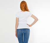 istock white t-shirt on a smiling girl : back view. Red hair woman with empty tshirt mock up 1221837235