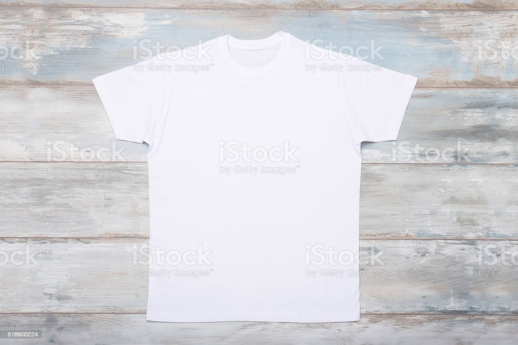White t-shirt on wooden floor stock photo