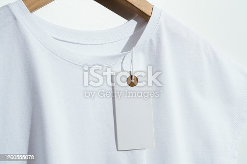 White t-shirt with blank price tag on wooden hanger