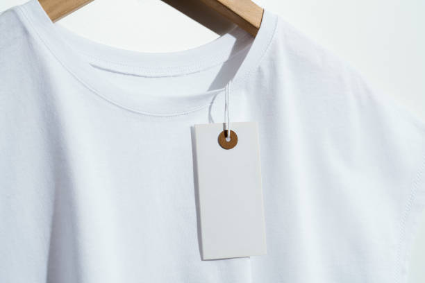 White t-shirt with blank price tag on wooden hanger stock photo