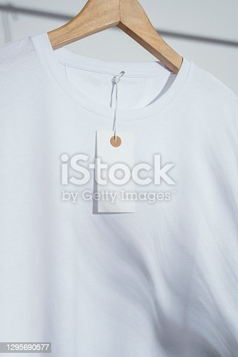 Blank white t-shirt with blank price tag mockup, template on wooden hanger