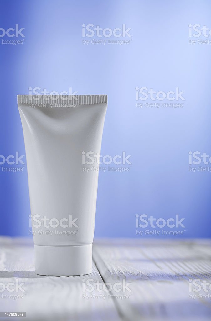 white tube on the table and blue background royalty-free stock photo
