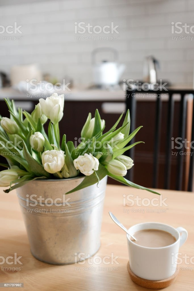 White tulips in an iron pot in the kitchen stock photo