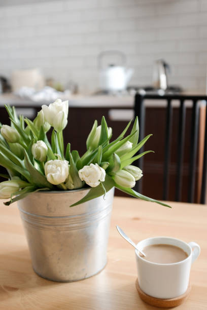 tulipes blanches dans un pot de fer dans la cuisine - motif ornemental photos et images de collection